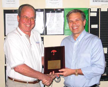 "Vecellio Group V.P. of Safety John West, left, presents Ranger South President Hazen Hinds with a plaque from Travelers honoring the division's impressive ""no lost time"" accomplishments."
